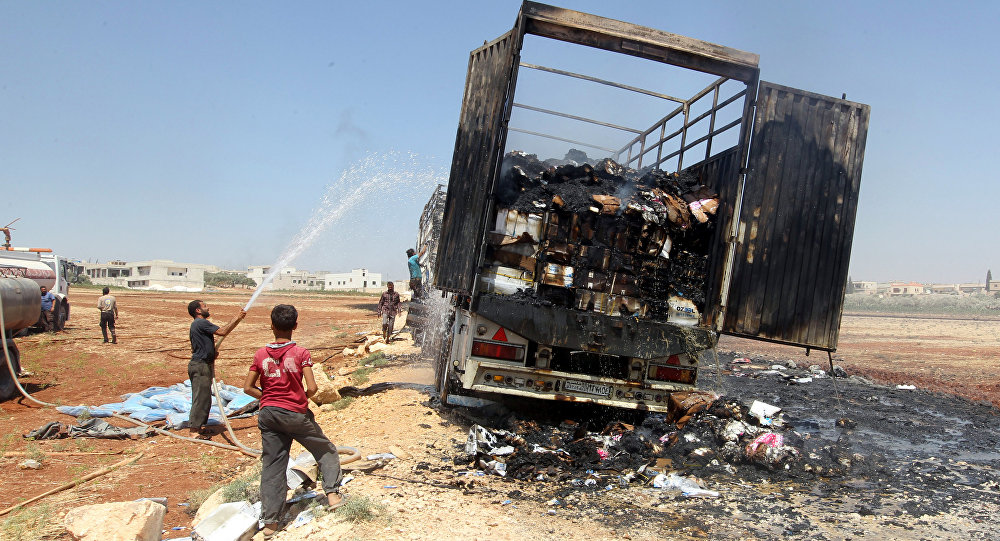 Men try to put out a fire of a loaded truck after an airstrike on a truck parking lot in the rebel-held town of Atareb in Aleppo province, Syria August 3, 2016