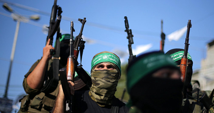 Hamas militants hold weapons.