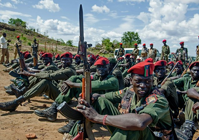 Sudan People's Liberation Army (SPLA) soldiers sit on the ground at a containment site outside of Juba (File)