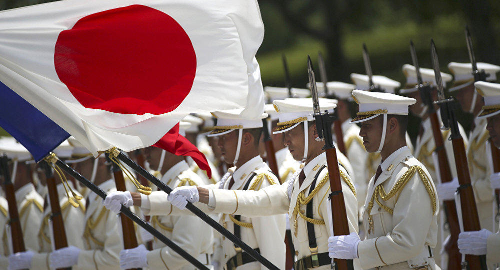 In this July 29, 2014 photo, members of a Japan Self-Defense Forces' honor guard prepare to be inspected by French Defense Minister Jean-Yves Le Drian at the Defense Ministry in Tokyo, Tuesday, July 29, 2014