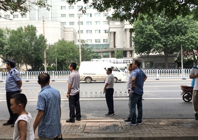 Chinese policemen in plain clothes stand as they stop journalists from taking pictures and video footage in front of the Number 2 Intermediate People's Court in Tianjin on August 4, 2016