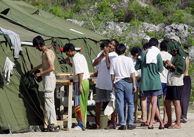 In this Sept. 21, 2001, file photo, men shave, brush their teeth and prepare for the day at a refugee camp on the Island of Nauru