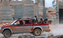 Fighters of the Syrian Islamist rebel group Jabhat Fateh al-Sham, the former al Qaeda-affiliated Nusra Front, ride on a pick-up truck in the 1070 Apartment Project area in southwestern Aleppo, Syria August 5, 2016