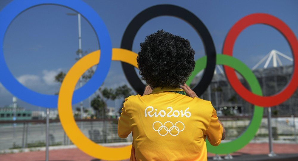 A man at the Olympic rings at the Olympic Park in Rio de Janeiro