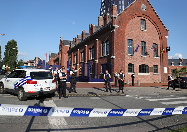Police stand as they secure the area around a police building in the southern Belgian city of Charleroi following a machete attack on August 6, 2016