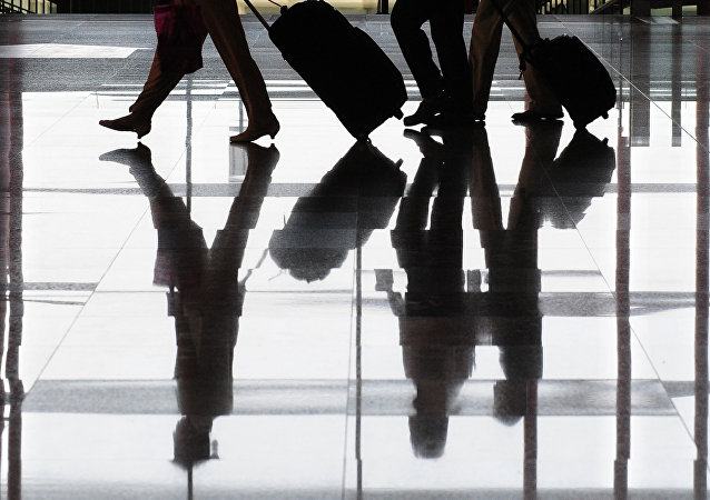 Travellers and their luggage are reflected on the floor at Terminal 3 of Beijing's Capital International Airport. (File)