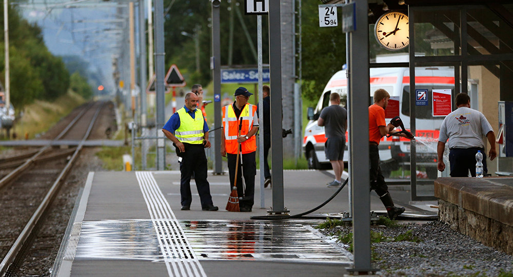 A Swiss police officer stands near workers cleaning a platform after a 27-year-old Swiss man's attack on a Swiss train at the railway station in the town of Salez, Switzerland August 13, 2016