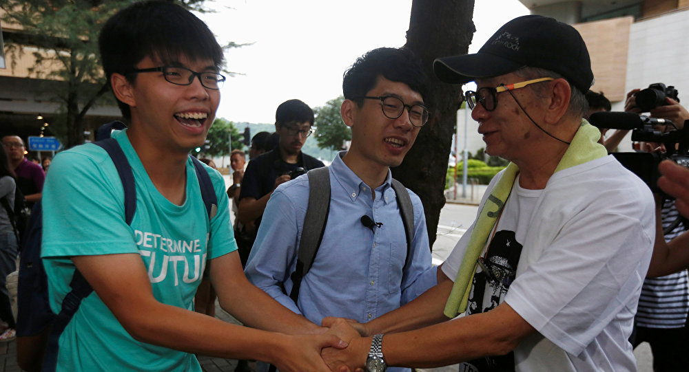 Student leaders Joshua Wong (L) and Nathan Law (C) are greeted by a supporter after a verdict, on charges of inciting and participating in an illegal assembly in 2014 which led to the Occupy Central pro-democracy movement, outside a court in Hong Kong August 15, 2016