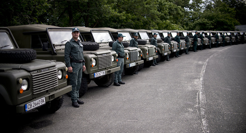 Bulgarian border police personal stand between military vehicles donated to Bulgarian government by the United Kingdom at the border between Bulgaria and Turkey near the Bulgarian town of Malko Tarnovo on May 22, 2016