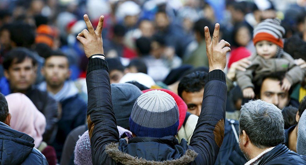 Migrants gesture after arriving at the Austrian-German border in Achleiten