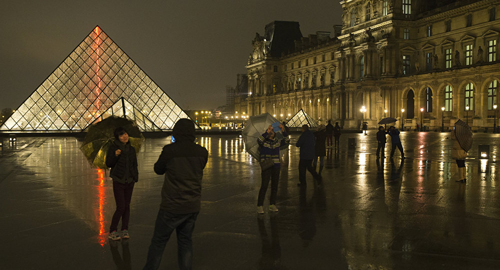 Chinese tourists take at night photos of each other outside the main entrance to the Louvre museum and its pyramid, on March 24, 2015 in Paris. (File)