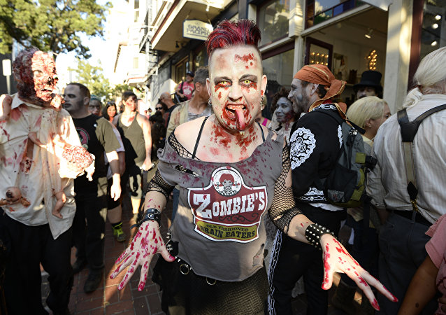 Zombies walk down Fifth Avenue as they take part in the Zombie Walk on day three of the Comic-Con International held at the San Diego Convention Center