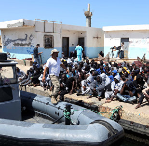 Illegal migrants sit on the dock at the Tripoli port after 117 migrants of African origins, including six pregnant women, were rescued by two coast guard boats off the coast of Libya on June 7, 2016