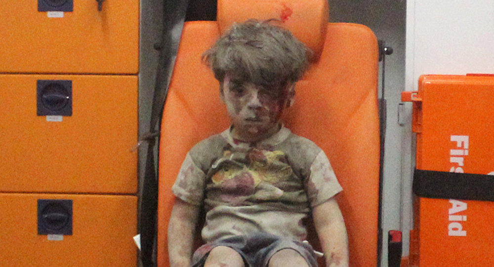 Five-year-old Omran Daqneesh, with bloodied face, sits inside an ambulance after he was rescued following an airstrike in the rebel-held al-Qaterji neighbourhood of Aleppo, Syria August 17, 2016