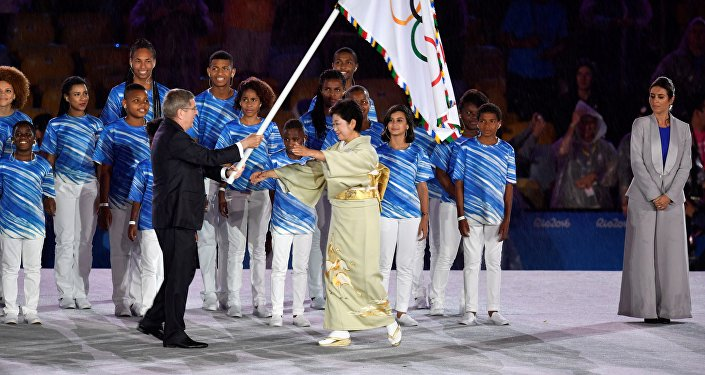 International Olympic Committee (IOC) President Thomas Bach (L) gives the Olympic flag to Tokyo's governor Yuriko Koike during the closing ceremony of the Rio 2016 Olympic Games at the Maracana stadium in Rio de Janeiro on August 21, 2016.
