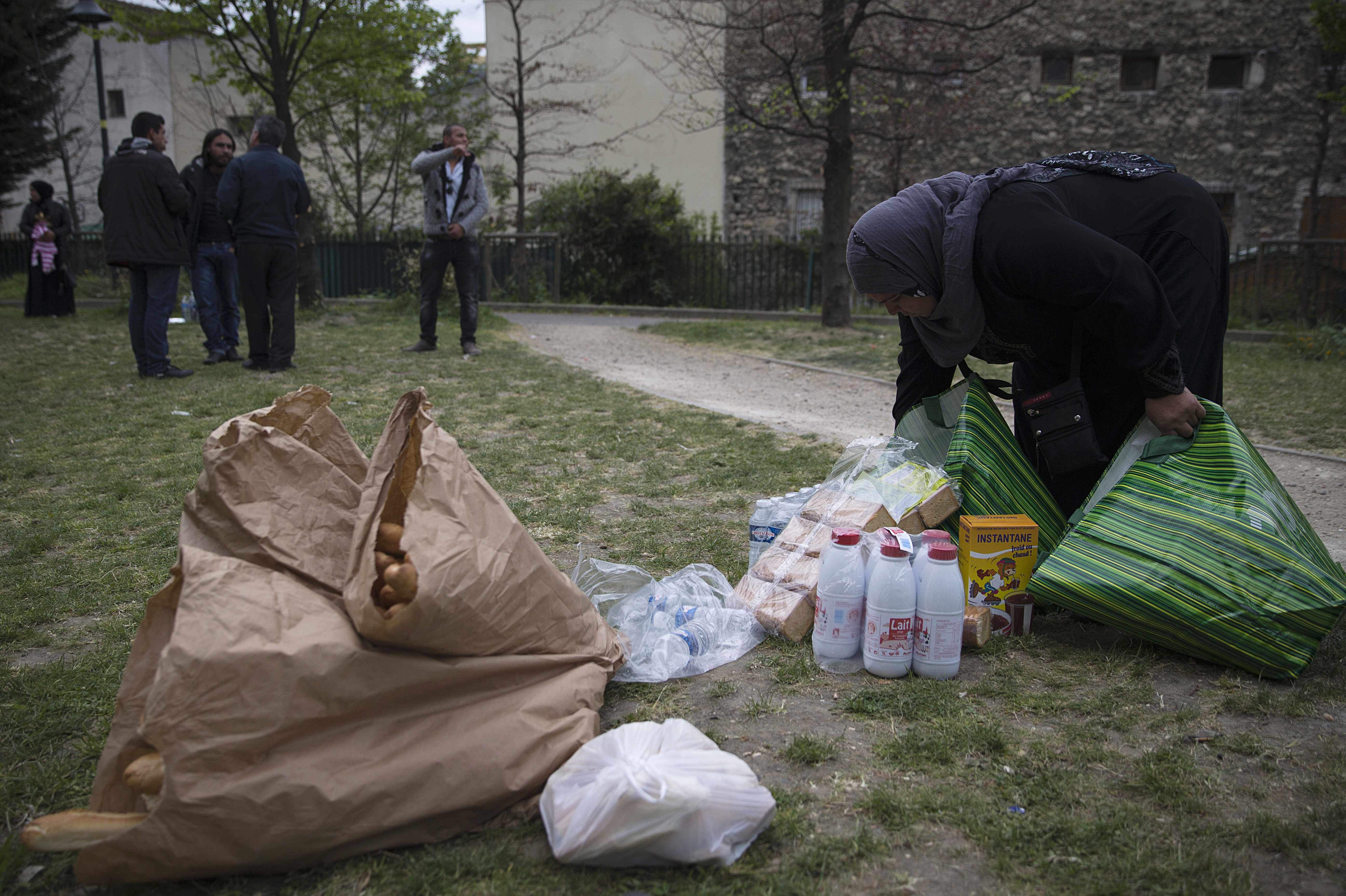 A Syrian refugee woman packs food on April 21, 2014 in the Edouard Vaillant park in Saint-Ouen, north of Paris, where the refugees spend most of their days awaiting to find housing solutions