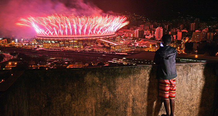 A boy from Mangueira favela watch fireworks over Maracana Stadium during the 2016 Olympics closing ceremony in Rio de Janeiro on August 21, 2016