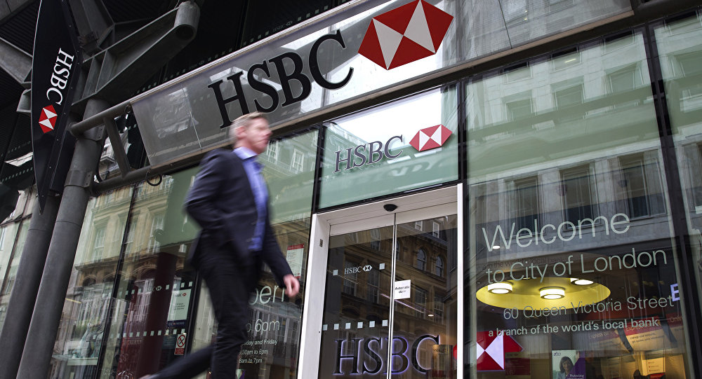 A businessmen walks past the entrance to a HSBC bank branch in London.