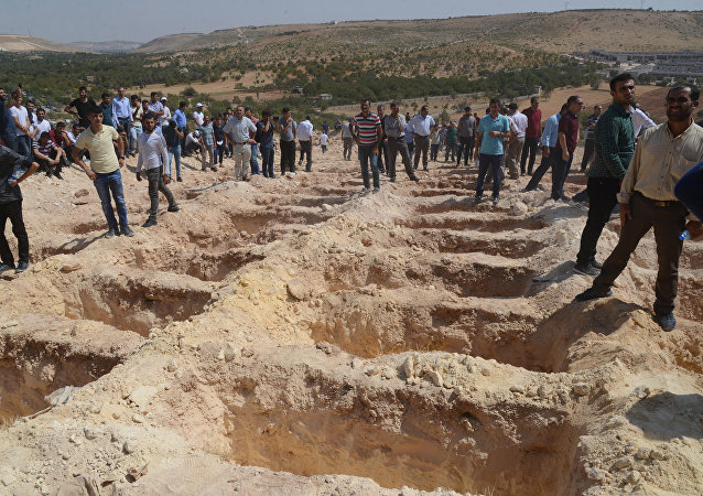 People wait close to empty graves at a cemetery during the funeral for the victims of last night's attack on a wedding party that left 50 dead in Gaziantep in southeastern Turkey near the Syrian border on August 21, 2016