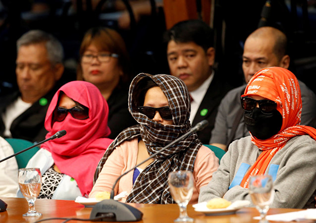 Family members of people alleged by police as drug pushers and were killed during an illegal drugs meth raid, wear masks during a Senate hearing regarding people killed during a crackdown on illegal drugs in Pasay, Metro Manila, Philippines August 23, 2016.