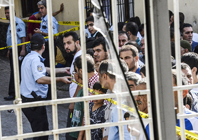 People stand near the explosion scene behind police cordon following a late night attack on a wedding party that left at least 30 dead in Gaziantep in southeastern Turkey near the Syrian border on August 21, 2016