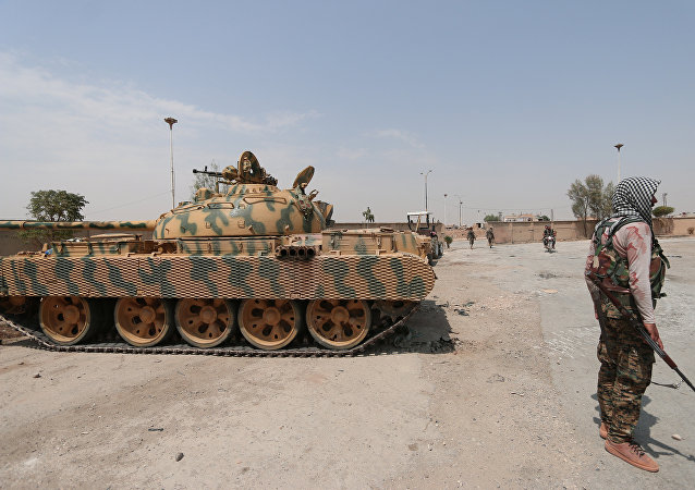 A Kurdish fighter from the People's Protection Units (YPG) carries his weapon as he stands past a tank in the Ghwairan neighborhood of Hasakah, Syria, file photo.
