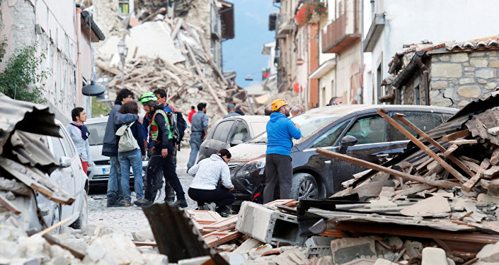 People stand along a road following a quake in Amatrice, central Italy, August 24, 2016.