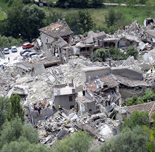 Rescuers search through debris of collapsed houses in Pescara del Tronto, Italy, Wednesday, Aug. 24, 2016