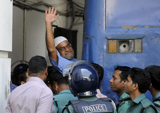 This file photograph taken on November 2, 2014, shows Bangladeshi Jamaat-e-Islami party leader, Mir Quasem Ali waving as he enters a van at the International Crimes Tribunal court in Dhaka