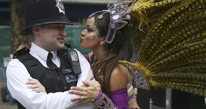A performer dances with police during the Notting Hill Carnival in London, Britain August 29, 2016.