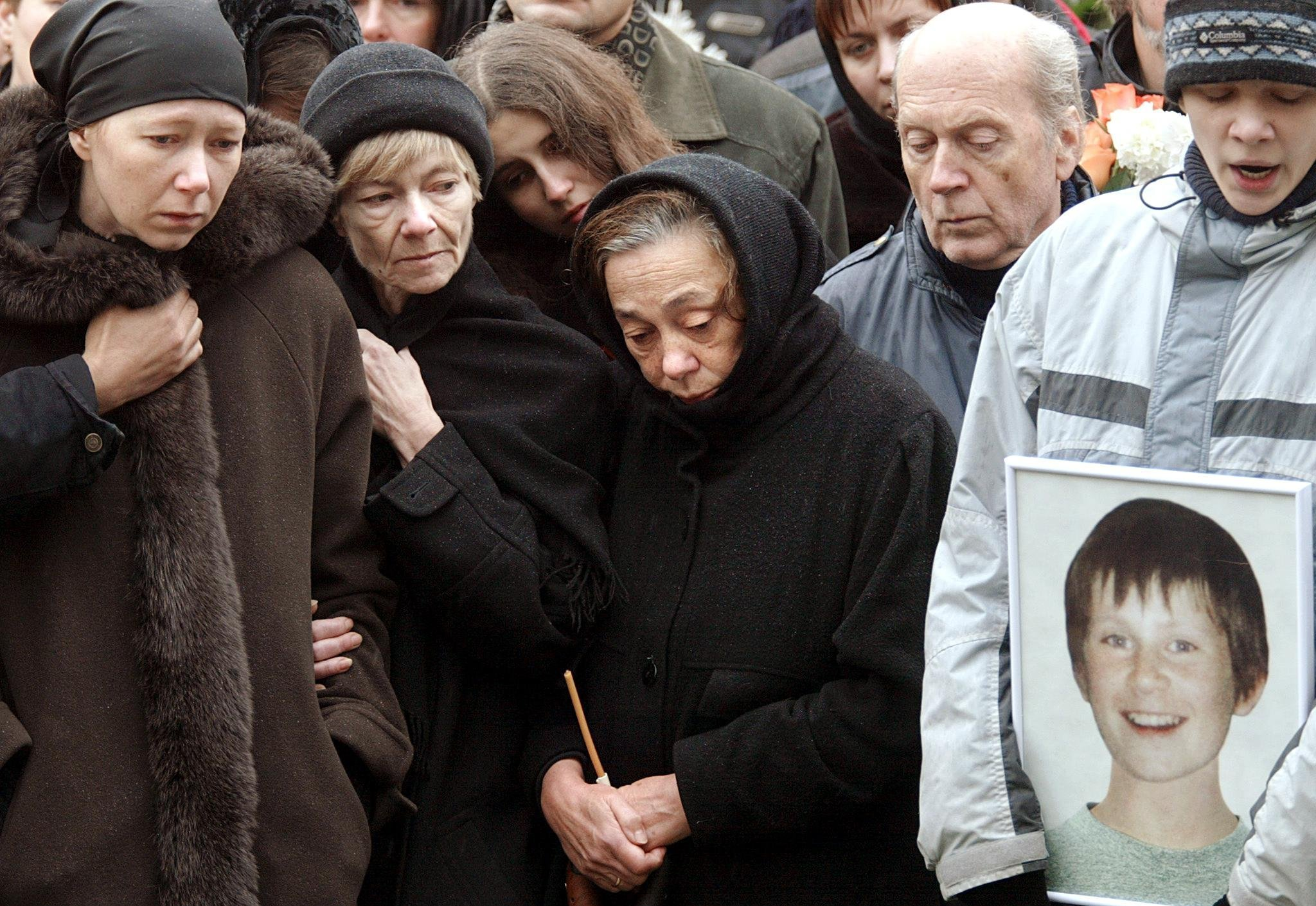 Relatives and friends of Arseny Kurilenko (portrait at R), 13, a member of the cast of the Nord-Ost show mourn during his funeral in Moscow, 30 October 2002. (File)