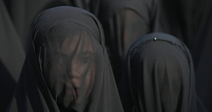 An Iraqi Shiite girl, whose face is covered with a veil, takes part in a parade in preparation for the peak of the mourning period of Ashura in Baghdad's northern district of Kadhimiya on October 22, 2015