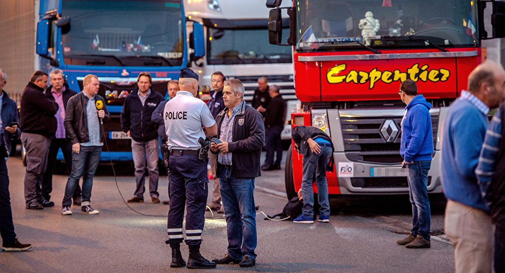 A man speaks with a police officer as a dozen of truck drivers gather in a parking on September 5, 2016 in Loon Plage prior to a slow-down operation on the A16 highway to ask for the dismantling of the so-called Jungle migrant camp in the French northern port city of Calais