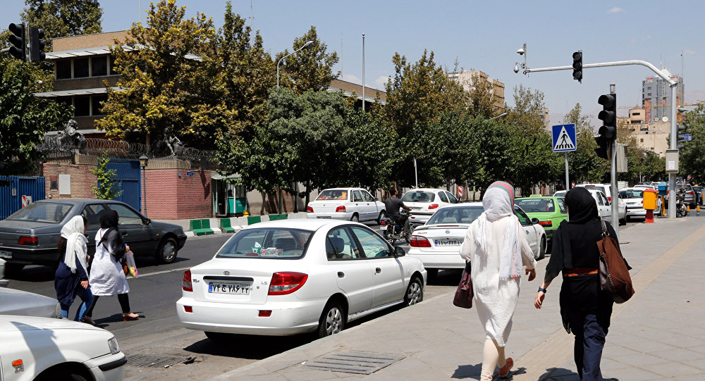 Iranians walk past the closed British embassy in the capital Tehran, on August 21, 2015