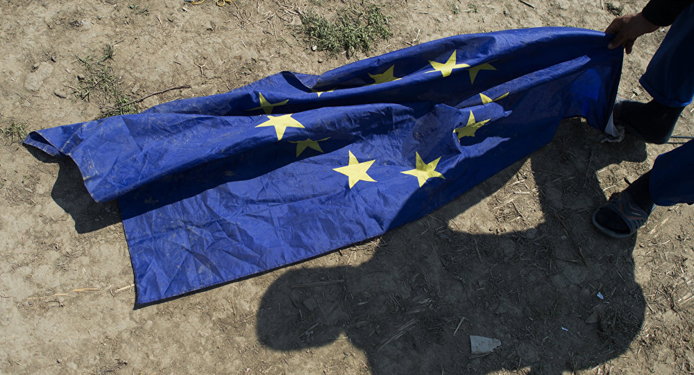 A migrant from Afghanistan grabs for an EU flag next to his tent at a makeshift camp for migrants and refugees near the village of Idomeni not far from the Greek-Macedonian border on May 1, 2016.