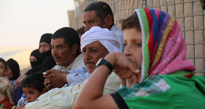 Iraqi families who fled Hawijah in northern Iraq, gather after arriving in the Kirkuk province, about 200 km north of the capital Baghdad, on August 7, 2016