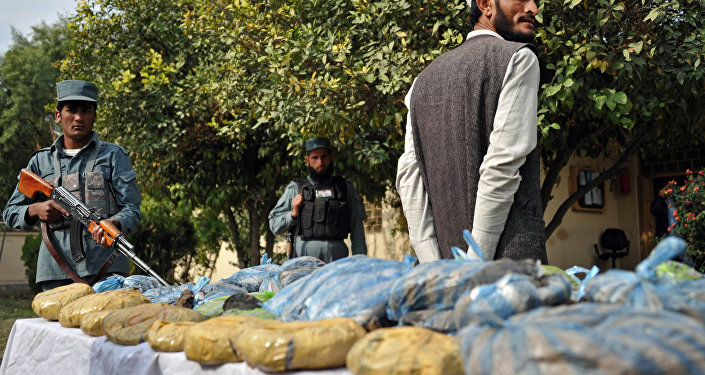 An Afghan policeman (L) stands guard as a detained suspect and bags containing heroin are presented to the media at a police station in Jalalabad on November 17, 2012.