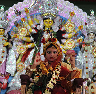 A young Indian Hindu unmarried girl, Nilanjana Chakraborty (5), known as a 'kumari' and dressed as the Hindu goddess Durga, puts her hand up during a ritual for the Durga Puja festival at Ramakrishna Mission in Agartala, the capital of northeastern state of Tripura on October 21, 2015