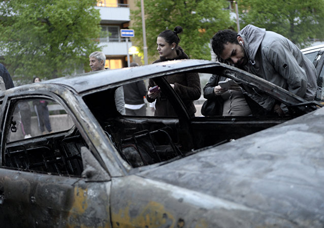 People inspect a car gutted by fire in the Stockholm suburb of Rinkeby