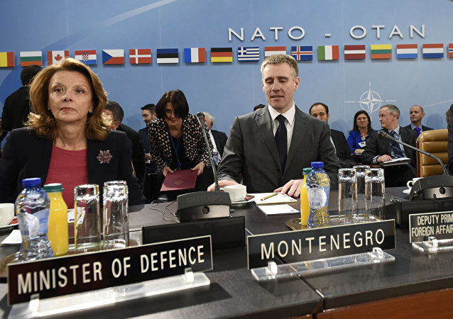 Montenegro's Foreign Minister Igor Luksic, center, Montenegro's Defense Minister Milica Pejanovic-Durisic, left, and NATO Secretary General Jens Stoltenberg prepare to address the North Atlantic Council at NATO headquarters in Brussels on Wednesday, Dec. 2, 2015