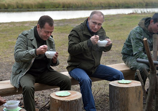September 10, 2016. Russian President Vladimir Putin, second right, and Prime Minister Dmitry Medvedev, left, have fish soup after a boat trip on Lake Ilmen, Novgorod Region.
