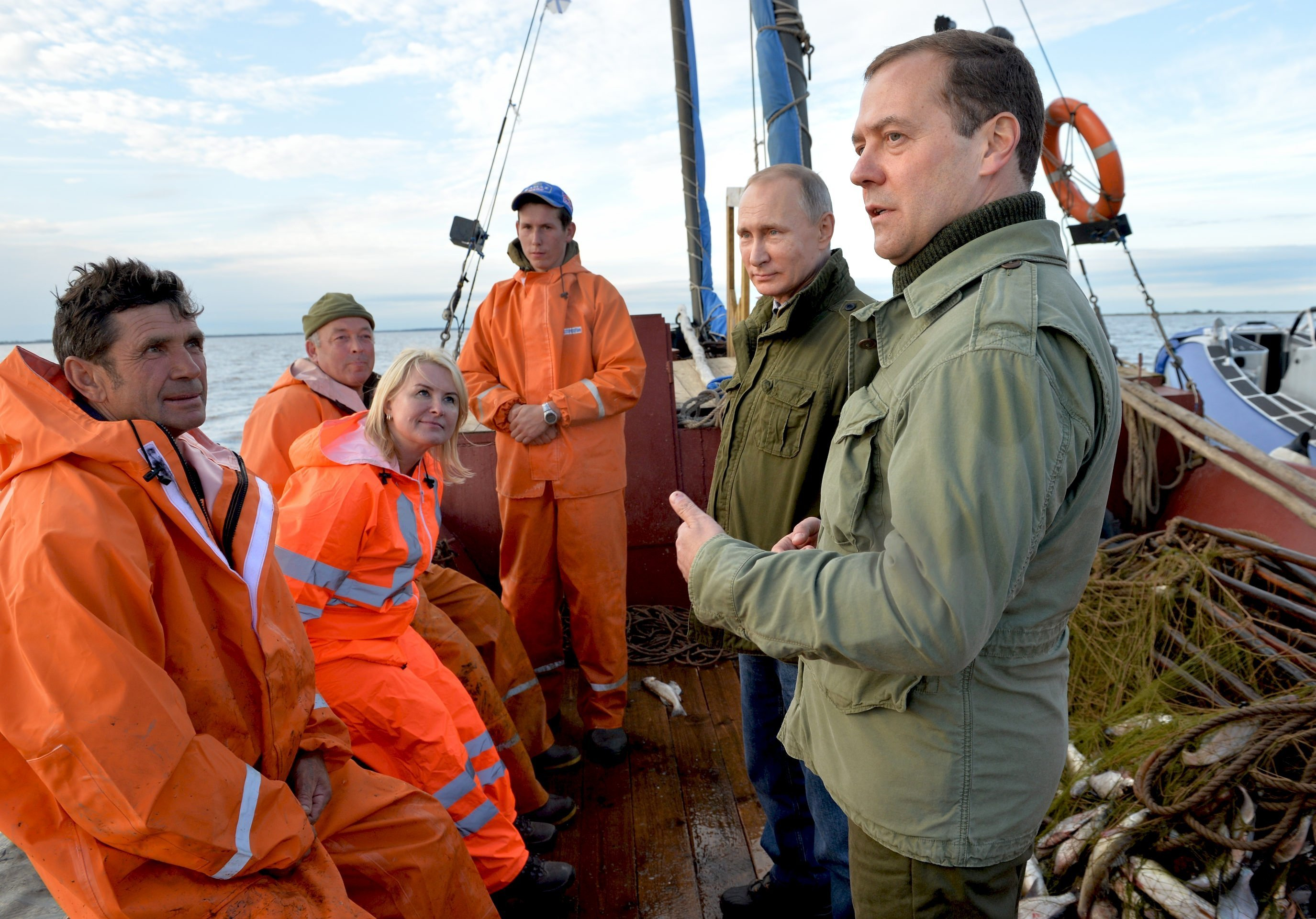 September 10, 2016. Russian President Vladimir Putin, second right, and Prime Minister Dmitry Medvedev, right, talk with fishermen during a boat tour of Lake Ilmen, Novgorod Region.