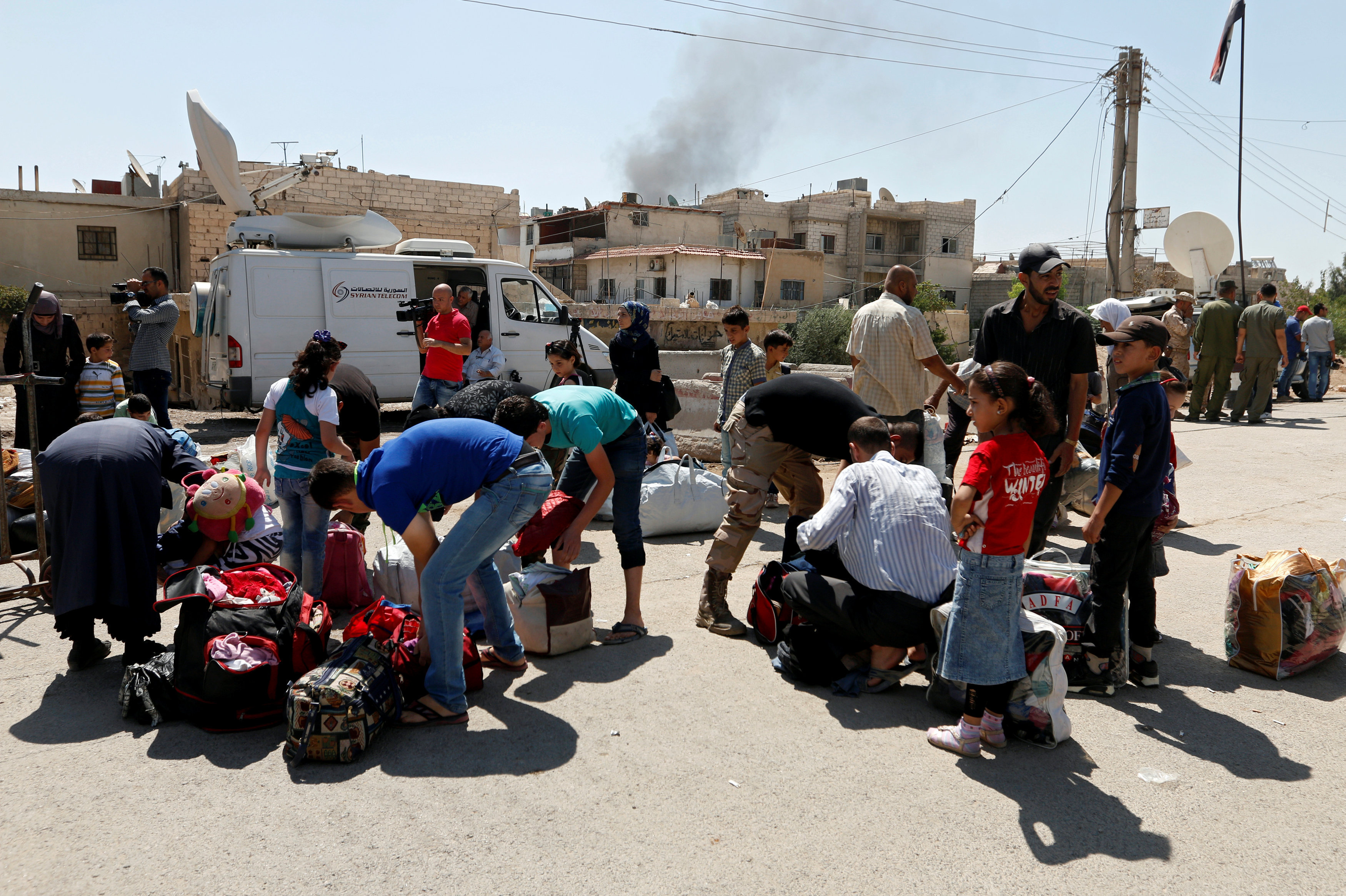 Civilians get their belongings inspected by Syrian Army soldiers in Daraya before being evacuated, after reports of an agreement between rebels and Syria's army to evacuate civilians and rebel fighters from Moadamiya, in Damascus, Syria September 2, 2016