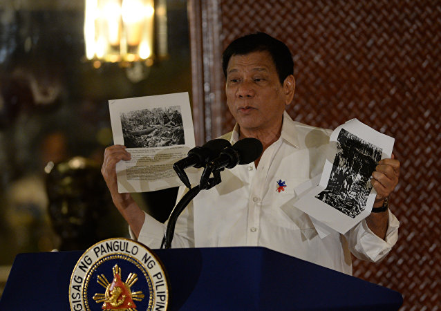 Philippine President Rodrigo Duterte holds up a photo and cites accounts of US troops who killed Muslims during the US's occupation of the Philippines in the early-1900s, during a speech at the Malacanang palace in Manila on September 12, 2016.