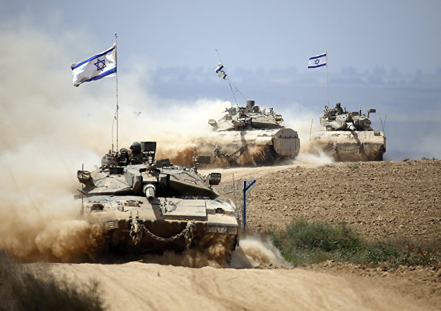 Israeli Merkava tanks roll near the border between Israel and the Gaza Strip as they return from the Hamas-controlled Palestinian coastal enclave on August 5, 2014
