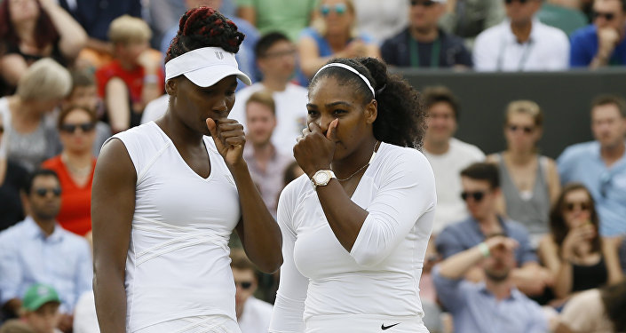 Serena Williams, right with her sister and playing partner Venus Williams of the US talks as they play against Elena Vesnina of Russia and Ekaterina Makarova of Russia during their women's doubles tennis match on eleven day of the Wimbledon Tennis Championships in London, Thursday, July 7, 2016