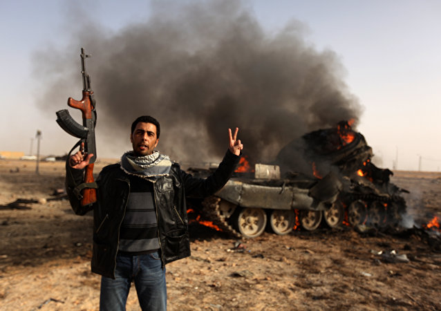 A Libyan rebel flashes a V-sign in front of burning tank belonging to loyalist forces bombed by coalition air force in the town of Ajdabiya on March 26, 2011