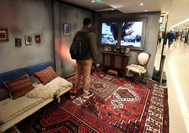 A man stands inside a Syrian house, which is part of an Amnesty International art installation to raise awarness of the conflict in Syria, at a subway station in Buenos Aires, Argentina, September 19, 2016