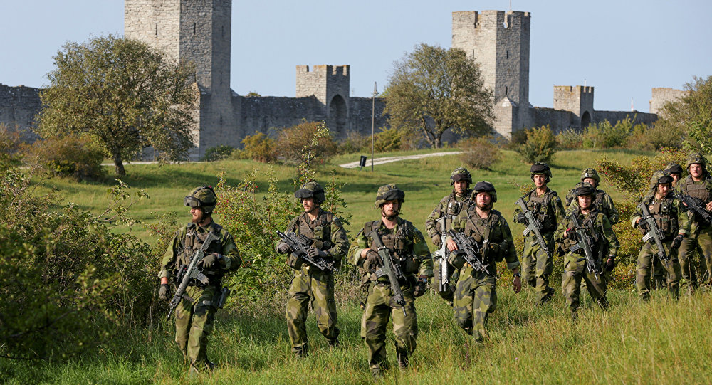 A squad from Skaraborg Armoured Regiment, currently training on the island of Gotland in the Baltic, patrols outside Visby's 13th century city wall, Sweden September 14, 2016