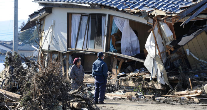 Local residents look at a damaged house caused by a tsunami in Minamisoma, Fukushima Prefecture.